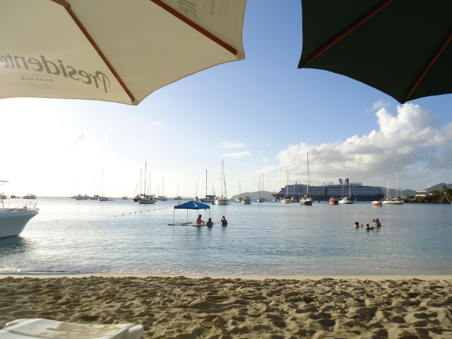 Enjoying Honeymoon Beach from under our umbrella with a cruise ship passing by the harbor.